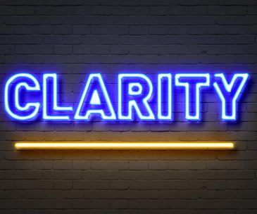 Clarity neon sign on brick wall background